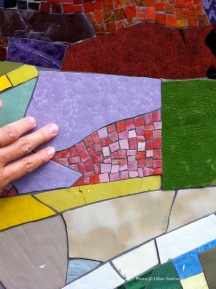detail of large and small pieces of glass smalti, hand for scale